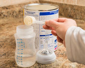 Mother preparing baby formula for infant — Stock Photo