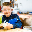 Parent draws stencil on wood block to be used as body for Pinewood Derby car — Stock Photo #38632109