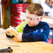 Parent draws stencil on wood block to be used as body for Pinewood Derby car — Stock Photo #38632121