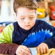 Parent draws stencil on wood block to be used as body for Pinewood Derby car — Stock Photo #38632159