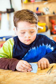 Parent draws stencil on wood block to be used as body for Pinewood Derby car — Stock Photo