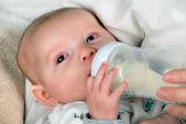 Infant baby feeding from bottle — Stock Photo