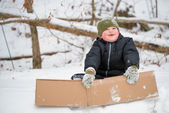 Child playing in snow using cardboard box to slide down hill — Stockfoto