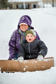 Mother and son playing in snow using cardboard box to slide down hill — Stok fotoğraf