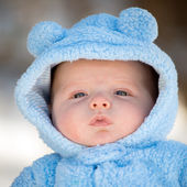 Cute infant baby boy wearing fluffy snow suit during winter — Stock Photo
