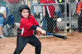 Young baseball player hitting ball off a tee during game — Stok fotoğraf