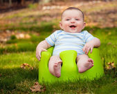 Happy infant baby boy using training Bumbo seat to sit up — Stock Photo
