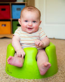 Baby boy using training Bumbo seat to sit up — Stock Photo