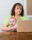 Mutter holding baby während der arbeit an ihrem computer — Stockfoto