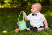Cute infant baby boy playing with Easter eggs and basket — Stock Photo
