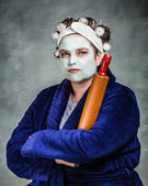 Mean and ugly housewife with facial mask, hair rollers and rolling pin — Stock Photo