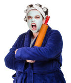 Mean and ugly housewife with facial mask, hair rollers and rolling pin isolated on white — Stock Photo