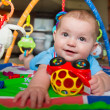 Happy and curious infant baby boy playing on activity mat — Stock Photo #47395403