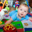 Happy and curious infant baby boy playing on activity mat — Stock Photo
