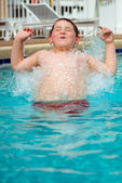 Young boy splashing into pool while swimming — Stock Photo