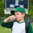 Child baseball player drinking chocolate milk after game — Stock Photo #47850033