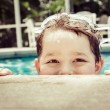 Young child peeking out of pool while swimming in vintage filtered image — Stock Photo #48390639
