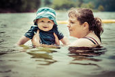 Mother teaching infant baby son to swim in lake during summer in — Stock Photo