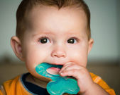 Baby chewing on teething ring toy — Stock Photo