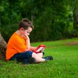 Young boy using tablet outdoors at park — Stock Photo #51311909
