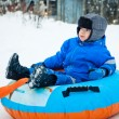 Stock Photo: Boy on snow tube