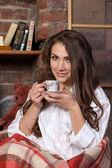 有一杯咖啡附近书架的漂亮女孩 — 图库照片