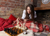 Girl play chess by fireplace — Stock Photo