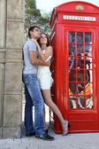 Amazing couple portrait near red telephone box — Stock Photo
