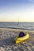 Fishing pole and canoe on the beach — Stock Photo