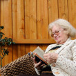 Senior woman reading outdoors — Stock Photo