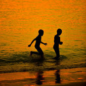 Silhouette little child on a beach at sunset — Stock Photo