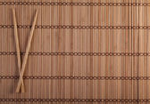 Two chopsticks on sushi background — Stock Photo