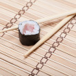 Foto Stock: Closeup sushi and chopsticks on bamboo mat