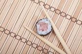 Closeup sushi and chopsticks on bamboo mat — Stock Photo