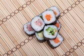 Closeup sushi roll on bamboo mat — Stock Photo