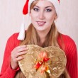 Royalty-Free Stock Photo: Young woman in Santa Claus hat with gift box