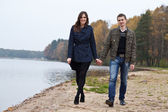 Young couple walking on lake — Stock Photo
