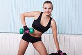 Lächelnd Sportlerin heben Hanteln — Stockfoto