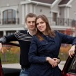 Stock Photo: Young family near car on background house