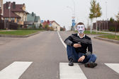 Hacker in masked members of Anonymous with mobile phone — Stock Photo