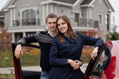 Young family near car on background house — Stock Photo