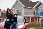 Young family near red car on background house — Stock Photo