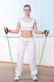 Fitness woman doing exercise with expander — Stock Photo