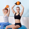 Two woman do exercises with hard ball — Stock Photo #15503377