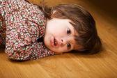 Маленькая девочка, лежа на полу — Стоковое фото