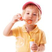 Little girl blows soap bubbles — Stock Photo