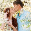 Kissing lovely couple in flower garden — Stock Photo #25764473