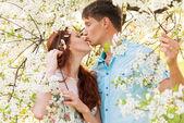 Kissing lovely couple in flower garden — Stock Photo