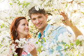 Romantic couple in flower garden — Stock Photo