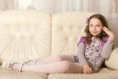 Fashion little girl lying on sofa — Stock Photo